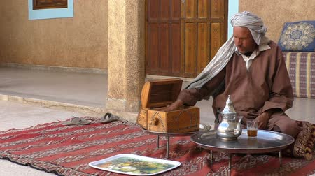 marrocos : TIOUT OR TIOUTE, TAROUDANT PROVINCE, MOROCCO, AFRICA - MARCH, 2016: Inside of an old Moroccan house. Berber man wearing traditional robe and turban sitting on a pillow on concrete floor is having his tea and preparing more tea for guests, putting sugar pi