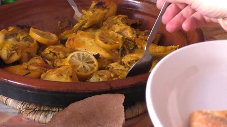 dish : Moroccan Berber guests taking pieces of lemon chicken tagine or tajine from ceramic dish in the middle of the table