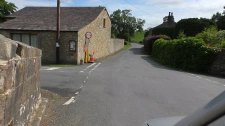 droga : Car front passenger POW while driving main road winding through English village over the old stone bridge and passing nice stone walled cottages into green hill sheep pasture Wideo