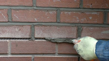habarcs : Close up of bricklayer working on brick wall crack repair.Long helibar is inserted into the gap after raking out old mortar and fresh mix tucked in using tuck pointing trowel.