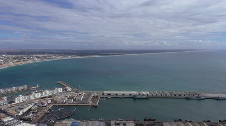 marrocos : Africa,Morocco, Agadir city on Atlantic coast panorama.Elevated view pan shows new white buildings, beach, sea, marina and industrial area of fishing port from above