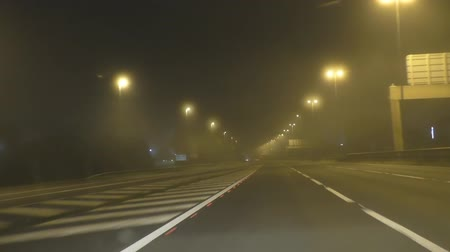 perigoso : Car drivers point of view driving on a foggy motorway in England with streetlights at night Vídeos