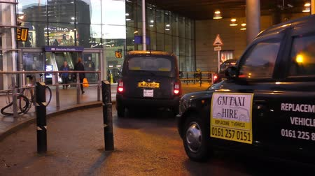 hackney carriage : MANCHESTER, ENGLAND, UK - FEBRUARY,  2017:  British symbol black cabs, hackney carriages or taxis entering through security gate barrier and picking passengers at the Piccadilly railroad station entrance. Stock Footage