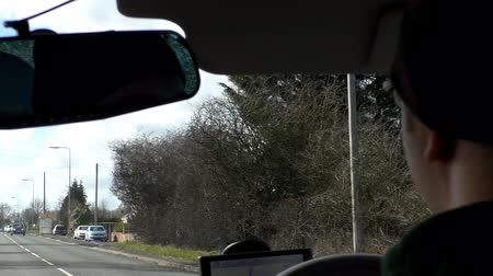 drive : Man is driving a car in rural area near Manchester, England using satellite navigation device.Windscreen view from inside of automobile.