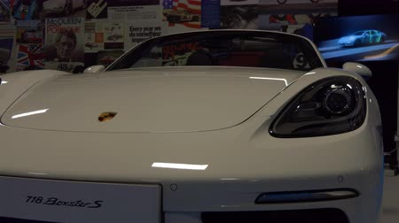 hall : MANCHESTER, ENGLAND, UNITED KINGDOM - APRIL, 2017: Porsche 718 Boxster S white car is on display in the dark hall with promotional video clip on the screen in background