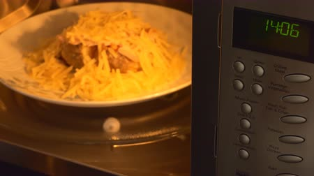mikrohullámú : Hand putting a plate with prepared for cooking jacket potato inside microwave then pressing buttons and oven starts working.Focus on keypad and display