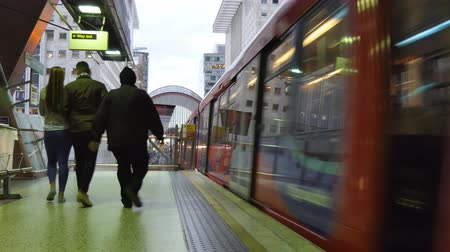 docklands : Rear view of young couple and man walking on platform, train is leaving Heron Quays station in London, UK Stock Footage