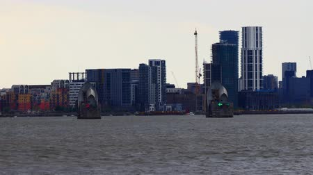 docklands : Zooming out from river Thames Barrier and London skyline behind it Stock Footage