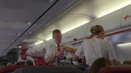 steward : MANCHESTER, ENGLAND, UNITED KINGDOM - OCTOBER, 2016: Scene in flight of jet2 aircraft. Cabin attendants, steward and stewardess are serving drinks to passengers Stock Footage
