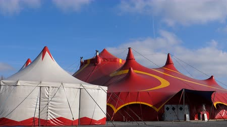 marquee : Two circus tents. White small and large red with closed entrance door on a sunny windy day
