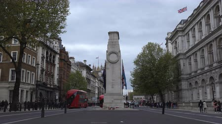 london cab : LONDON, ENGLAND, UNITED KINGDOM - APRIL, 2017: Central London city of Westminster war memorial, The Cenotaph in the middle of Whitehall. Great Britain flag or Union Jack on memorial and on the top of building Stock Footage