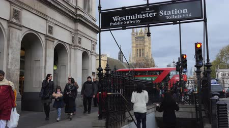 westminster : LONDON, ENGLAND, UNITED KINGDOM - APRIL, 2017: People passing entrance subway to London Underground or metro station of Westminster; suspicious man with beard wearing long leather coat wandering around