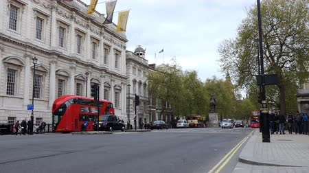 двойной : LONDON, ENGLAND, UNITED KINGDOM - APRIL, 2017: Street scene in the heart of United Kingdoms City of Westminster, Central London, showing the Banqueting House, famous red double-decker buses and taxis on Whitehall