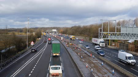 greater : MANCHESTER, ENGLAND, UNITED KINGDOM - MARCH, 2018: High angle view of Manchester Ring Road M60 being built into smart motorway.Traffic passing roadworks and unfinished construction of gantry