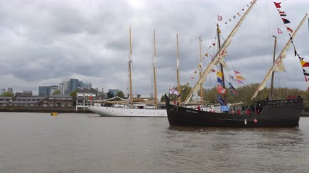 регата : LONDON, ENGLAND, UNITED KINGDOM - APRIL, 2017: Handheld camera view of two Portuguese old sailing tall ships on Thames river, white color lugger Santa Maria Manuela and caravel Vera Cruz, financial district skyscrapers seen in the background