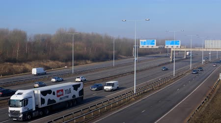 muller : MANCHESTER, ENGLAND, UNITED KINGDOM - MARCH, 2018: High angle view of sunlit transport moving on multi-lane Manchester Ring Road M60 in the light morning haze; Muller milk dairy product truck driving by Stock Footage