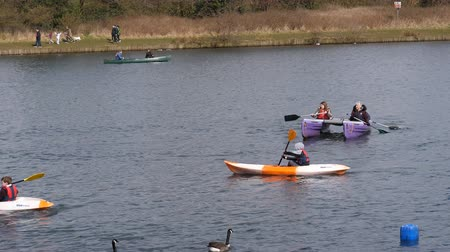 szórakozási : MANCHESTER, ENGLAND, UNITED KINGDOM - APRIL, 2018: On a nice spring day families enjoying paddling boats, kayaks or canoes on a lake, walking or riding bicycles on lakeside Stock mozgókép
