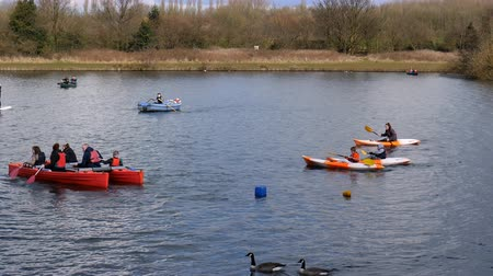 каноэ : MANCHESTER, ENGLAND, UNITED KINGDOM - APRIL, 2018: Families, adults and children paddling boats, canoes and kayaks on the lake on a nice spring day