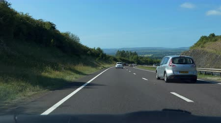 rota : NORTH WALES, UNITED KINGDOM - JUNE, 2017: Car front interior panel and windshield view of picturesque route while driving A55 highway in North  Wales on a sunny summer day Vídeos