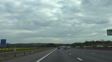 motoring : Car front window or driver view driving M1 motorway highway in England past yellow field on a cloudy day Stock Footage