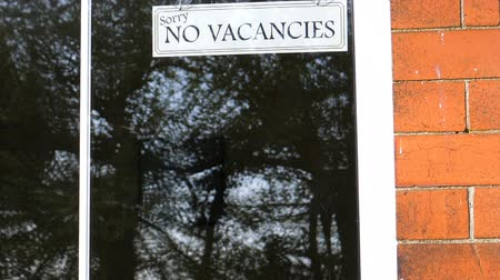 vaga : No Vacancies sign in a window of hotel or B&B tilt down, trees reflection on the glass Vídeos