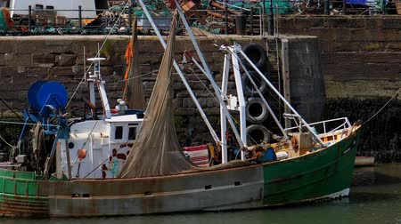 industrial fishing : Side view of an old fishing boat docked in scrapyard by the wall Stock Footage