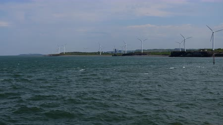 great britain : Wind farm turbines spinning on the seashore of Irish Sea on the coastline in Northwest of England.View from the sea Stock Footage