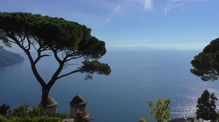 amalfi : Spectacular Amalfi coast scenery in Italy, view from above of blue Tyrrhenian sea and sky behind pine tree and old church belfry top Stock Footage