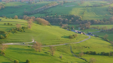 английский парк : Magnificent Peak District National Park scenery from hilltop in the evening. Cars driving rural road, hills and village in a valley lit by sun before sunset Стоковые видеозаписи