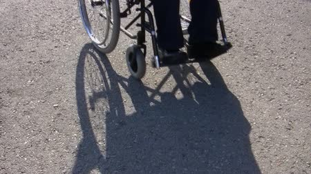 plain : On a sunny day man, wheelchair user and his shadow is coming towards the camera on plain asphalt background Stock Footage