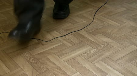 tripping : Legs of man in suit walking in the office and falling over hanging telephone cable. Health and safety at work or home concept