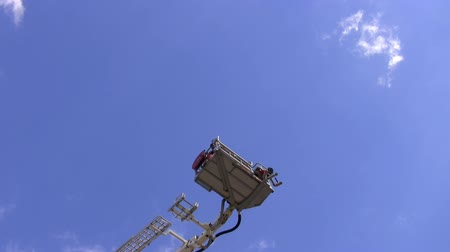 hydraulic : Telescopic firefighters aerial ladder platform is raising with people in it. Blue sky background