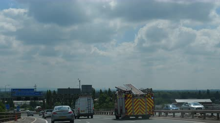 бросаясь : MANCHESTER, ENGLAND, UNITED KINGDOM - SEPTEMBER, 2018: Car windshield view driving on motorway M60, city ring road.Fire engine truck and ambulance rushing with emergency lights flashing.Handheld shot