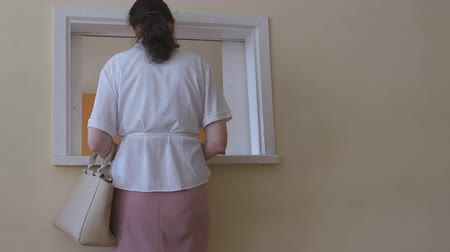 bum : Tall middle aged woman in summer clothing standing at the small office window for customers, patients, employees etc in Eastern European country