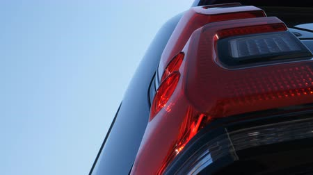 ambition : Slow diagonal tilt shot from car left side rear lights towards blue sky. Car of my dreams concept Stock Footage