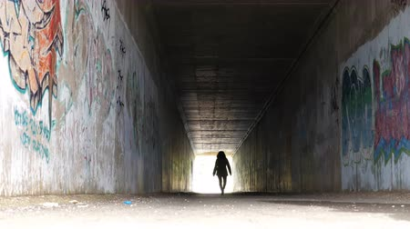hátsó megvilágítású : One woman walking slowly in the tunnel in daytime toward bright light at the exit