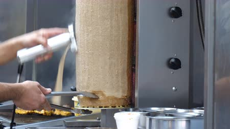 provést : Chef at take-away shop or take-out restaurant is slicing doner donner kebab meat from rotating spit using electric knife Dostupné videozáznamy