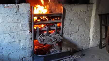charcoal stove : Coal and wood burning in an open brick and iron stove in ancient kitchen in United Kingdom