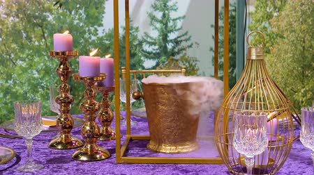 establishment : Purple and golden color colour dinner setting with burning candles and liquid nitrogen steaming from golden bucket for champagne Stock Footage