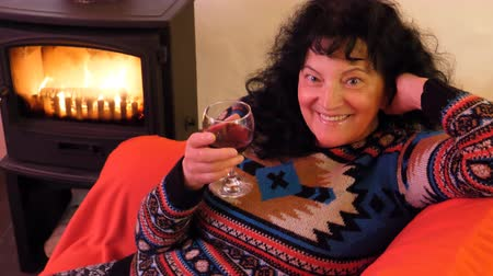 şarap kadehi : Middle aged long haired woman in knitted sweater sitting on red armchair or sofa drinking wine and smiling; says cheers while looking at the camera