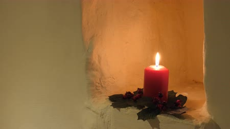 azevinho : Close up of decorated for Christmas red candle burning in the wall niche