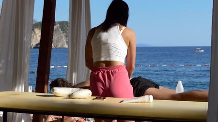 столовая гора : Unrecognizable woman masseuse is gently massaging back of man lying in the shade of spa treatment marquee or canopy on the beach, slow motion