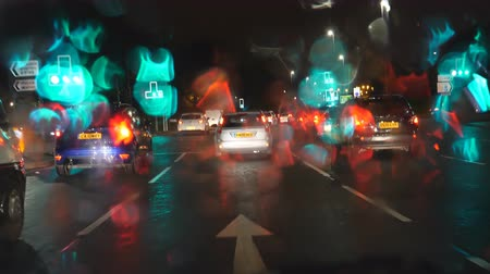 kasaba : LIVERPOOL, ENGLAND, UNITED KINGDOM - NOVEMBER, 2018: Car windshield view driving on rainy night A580 road from Liverpool city to Manchester, United Kingdom. Rain drops on windscreen glass make nice light flare effect