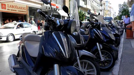 motorcycles : HERAKLION, CRETE ISLAND, GREECE - OCTOBER, 2014: Close up of row of motorcycles on a busy city centre center street Stock Footage