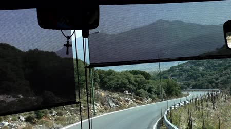 inside bus : Tourist bus front window view traveling winding mountain road toward Lasithi Plateau in Crete island of Greece, Europe. Little shrine on the roadside after bend on 10-12 sec.