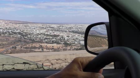 fas : Moroccan Agadir city panorama from inside of car driving on the hillside road, high angle view
