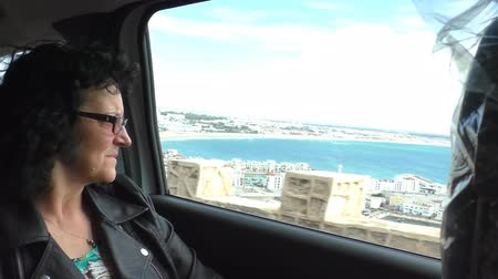 марокканский : Woman tourist sitting in the moving car enjoying high angle view of Atlantic ocean Moroccan coast city Agadir, she is looking and talking to camera Стоковые видеозаписи