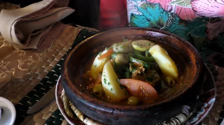 марокканский : Woman at the table in Moroccan cafe is waiting for hot steaming vegetarian tajine or tagine cooling off