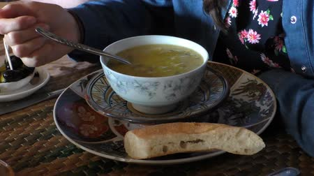 fas : Young woman starting eating hot steaming fish soup at the Moroccan cafe, close up