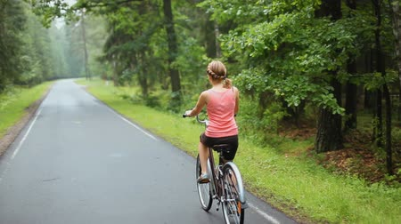 ona : A Young Woman Rides a Vintage Brown Bike on a Forest Road After a Rain in Summer. She Wears Shorts and Pink Top